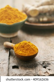Turmeric powder in wooden spoon on old wooden background.
