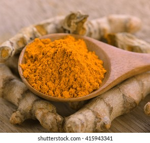 Turmeric  powder in  wooden spoon on wooden