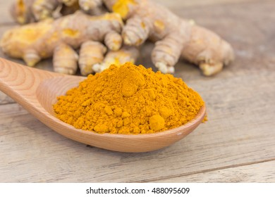 Turmeric powder in wooden spoon and turmeric on wood desk