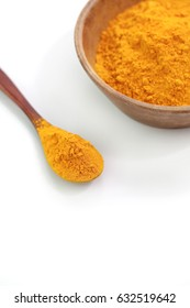 Turmeric powder in wooden spoon on white background