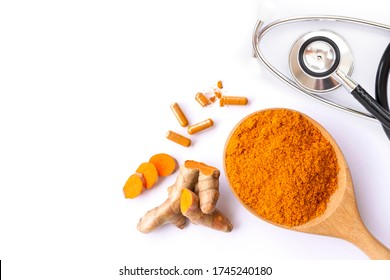 Turmeric powder in wooden spoon, tumeric root, curcumin capsule and medical stethoscope isolated white background. Top view. Flat lay.