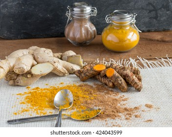 Turmeric and turmeric root with ginger and ground ginger - black slate background, fancy bottles