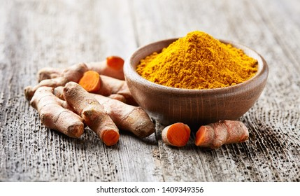 Turmeric root and powder on wooden board