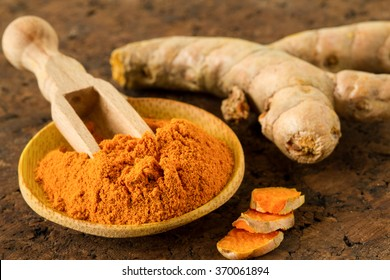 Turmeric root and turmeric powder on wooden background