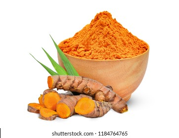 turmeric root and turmeric powder in the wood bowl with green leaves isolated on white background