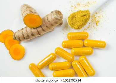 Turmeric root with yellow capsules and a spoonful curcuma powder on a white plate