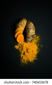 Turmeric roots and turmeric powder isolated on black background