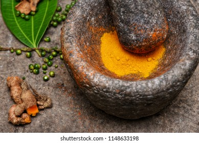 turmeric roots and powder in a mortar Kerala South India. Traditional Indian kitchen using vintage grinder for powdering spices which is used widely in curry and antiseptic Ayurveda treatments