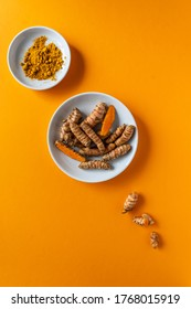 Turmeric roots and pzlver on two white plates. Orange background, healthy eating, flat lay, curcumin