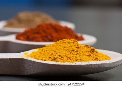 Turmeric, tandoori and garam masala on wooden spoons - shallow depth of field