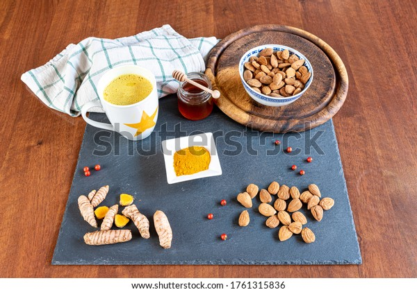 Turmeric tea or golden milk has been venerated since ancient times for its healing properties. Table set with ingredients