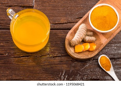 Turmeric and water, healthy drink - Wooden background