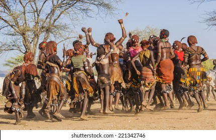 TURMI, OMO VALLEY, ETHIOPIA - DECEMBER 30, 2013: Unidentified group of Hamar women dance at bull jumping ceremony. Jumping of the bull is a rite of passage into manhood for some Omo Valley tribes.