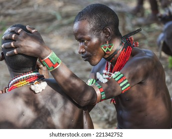 TURMI, OMO VALLEY, ETHIOPIA - DECEMBER 30, 2013: Unidentified Hamar men paint each other's face in a preparation to a bull jumping ceremony. Jumping of the bull is a rite of passage into manhood.