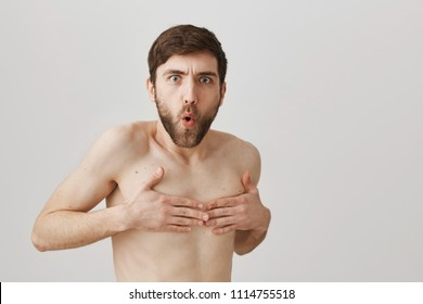 Turn around don't you see I am naked. Funny european man with beard standing naked over gray background and covering nipples with hands, expressing embarrassment and offence, being caught undressed