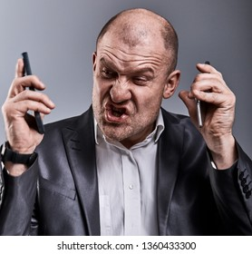 Turn nasty loud crying angry business man talking on two mobile phone very emotional in office suit on grey background. Closeup toned color portrait