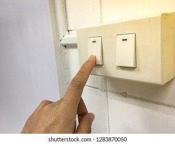 turn off the light, finger pressing on switch button to reduce energy using.