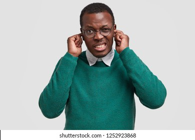 Turn off this loud music. Displeased black man pluggs ears with index fingers, frowns face, wears green sweater, isolated over white background. Annoyed African American guy ignores someone.