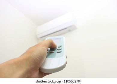 Turn on and off a white air conditioner in a room