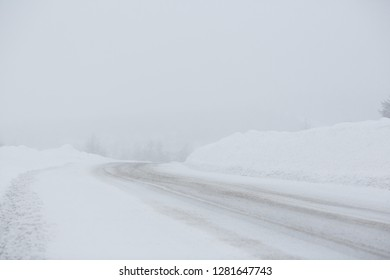 Turn on a snowy road. Snowfall and large snowdrifts. Cold and snowy weather. The roadway is covered with snow. Niveous winter. Kolyma Highway, Magadan Region, Far East Russia. Perfect for background.