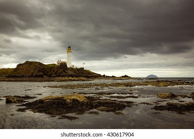 Turnberry Lighthouse under grey clouds from the rocks offshore at low tide.