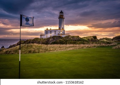 TURNBERRY POINT LIGHTHOUSE, SCOTLAND UK - AUGUST 09, 2018: Turnberry point lighthouse at championship golf course with red evening sky, rocks, ocean and restaurant.