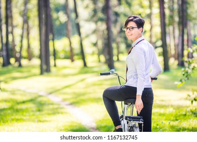 Turned around young woman sitting on her bike in a pine forest
