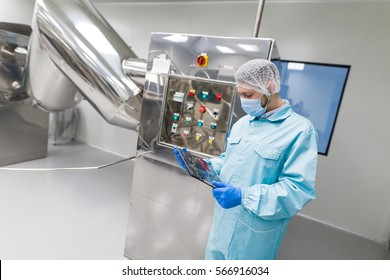 turned, close look of factory worker in blue lab suit controling how rotation machine works