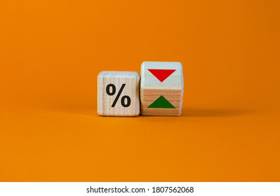 Turned a cube and changed the direction of an arrow symbolizing that the interest rates are going down or vice versa. Beautiful orange background. Business concept. Copy space.