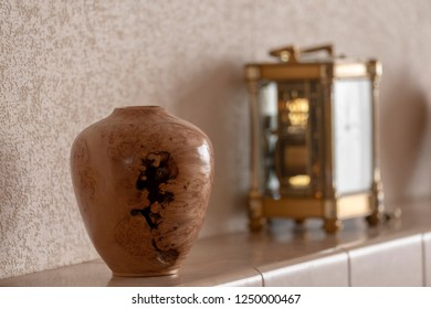 Turned elm burr vase positioned on tiled mantle piece with antique clock in background.