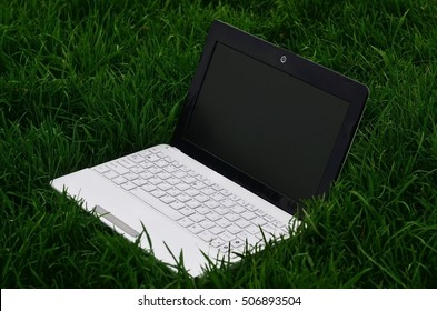 Turned off notebook on green field