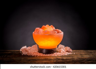 Turned on Himalayan pink salt lamp on a wooden table