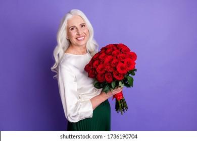 Foto alterada de una alegre y satisfecha anciana sosteniendo un gran ramo de rosas, recibe a su esposo de la familia la celebración del 14 de marzo con ropa de buen aspecto aislada sobre fondo de color violeta