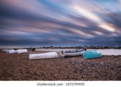 Up turned row boats on a stoney beach in Suffolk. Long streaky clouds from a long exposure