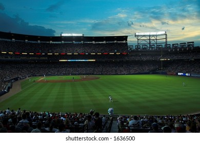 Turner Field, home of the Atlanta Braves, during a night game with capacity crowd; set against a brilliant blue sky