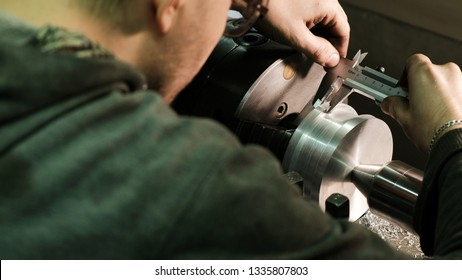 Turner measures the dimensions of the metal workpiece with a caliper. Work on a lathe