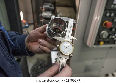 Turner miller verifies the accuracy of manufacturing steel parts with a special caliper Additional scale - the size of the measurement device. In the background to blur milling machine.