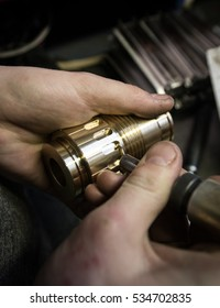 Turner removes burrs from brass parts after milling operations