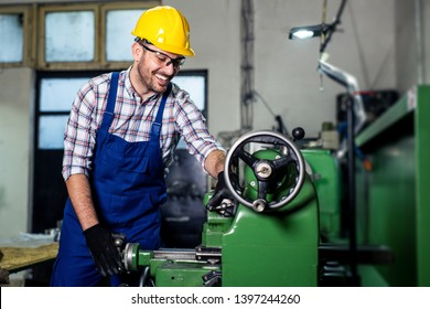 Turner worker is working on a lathe machine in a factory.