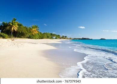 Turners Beach in Antigua mit tiefblauem Himmel und türkisfarbenem Wasser.