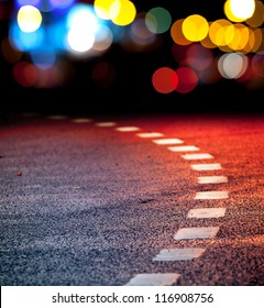 Turning asphalt road with marking lines and reflections with colorful unfocused lights on a background