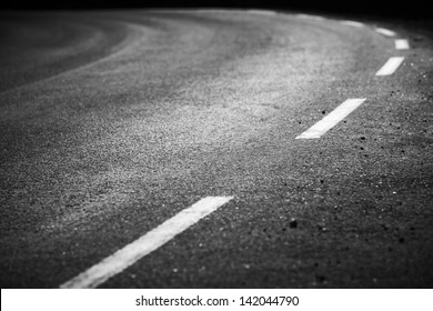 Turning asphalt road with marking lines and tire tracks. Close up photo with selective focus