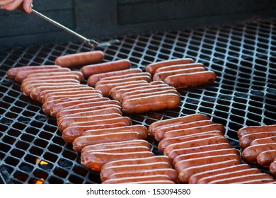 Turning Hot Dogs cooking on a large grill