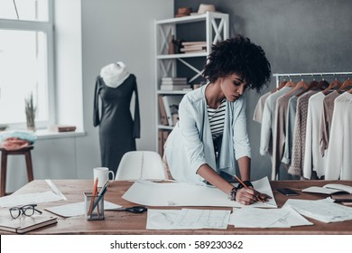 Turning ideas into clothing. Beautiful young African woman working on sketches while standing in her studio near the clothes hanging on the racks