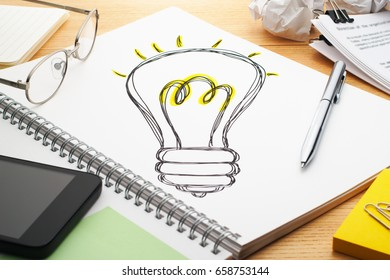 Turning on the light bulb. Drawing light bulb on notebook. Creating ideas. Notebook, pen, smartphone, glasses and document on wood table.