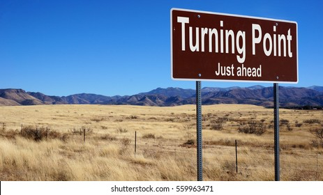 Turning Point Just Ahead  brown road sign with blue sky and wilderness