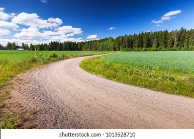 Turning rural road goes near green field under blue sky in summer day. Empty landscape background, Finland