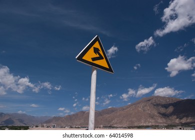 turning sign on yellow metal signboard against blue sky