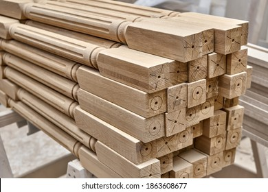Turning wooden stair balusters. Wood stair balusters stacked after sanding in workshop