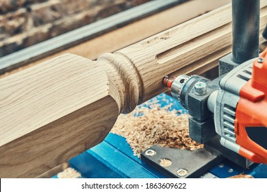 Turning wooden stair balusters. Wood stair balusters manufacturing process on a turning lathe with milling cutter. Close-up